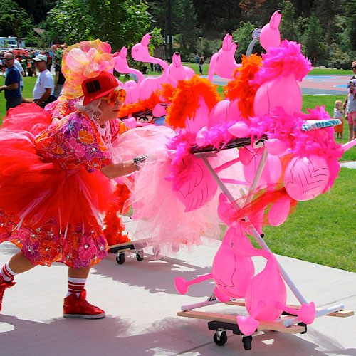 Woman in costume pushing pink flamingo prop