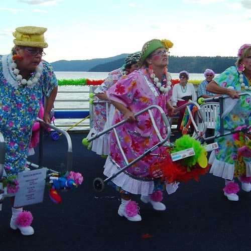 Women in front of lake performing with walkers