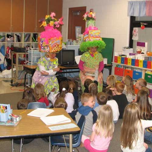Women in costume speaking with children in classroom