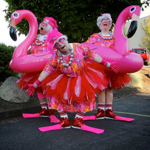 Women posing in pink with inflatable flamingos