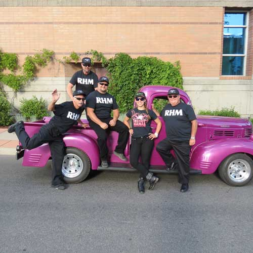 Men posing with classic pink truck