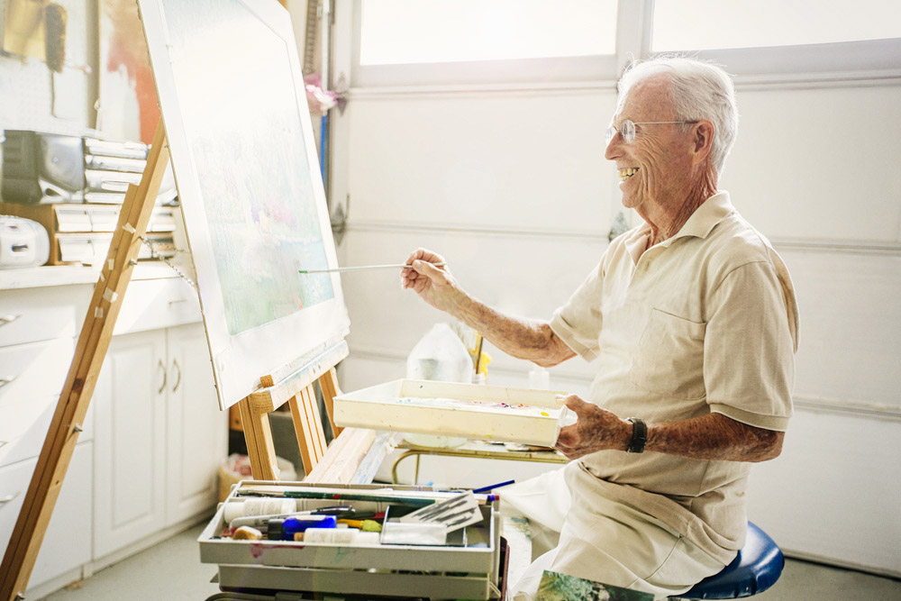 Older man in garage painting.