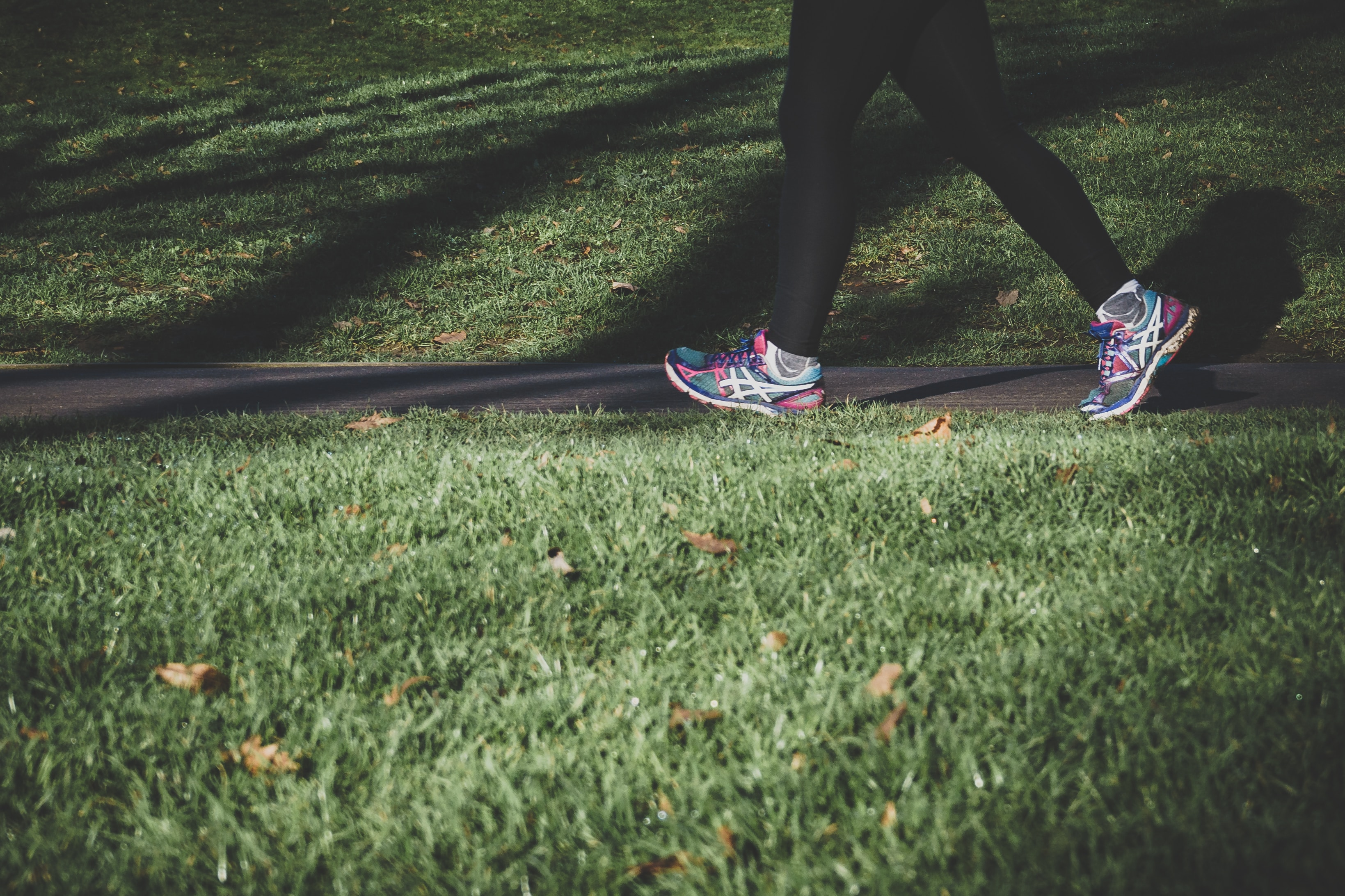 A photo of a person's legs as they walk on a trail between two grassy fields