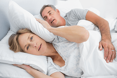 Wide awake wife trying to block out her husband's snoring with a pillow over her ears.