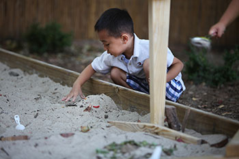 preschool student digging in sandbox