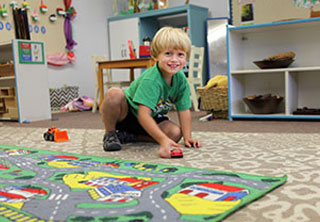 Preschool boy playing with car on floor