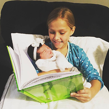 girl reading to baby sister