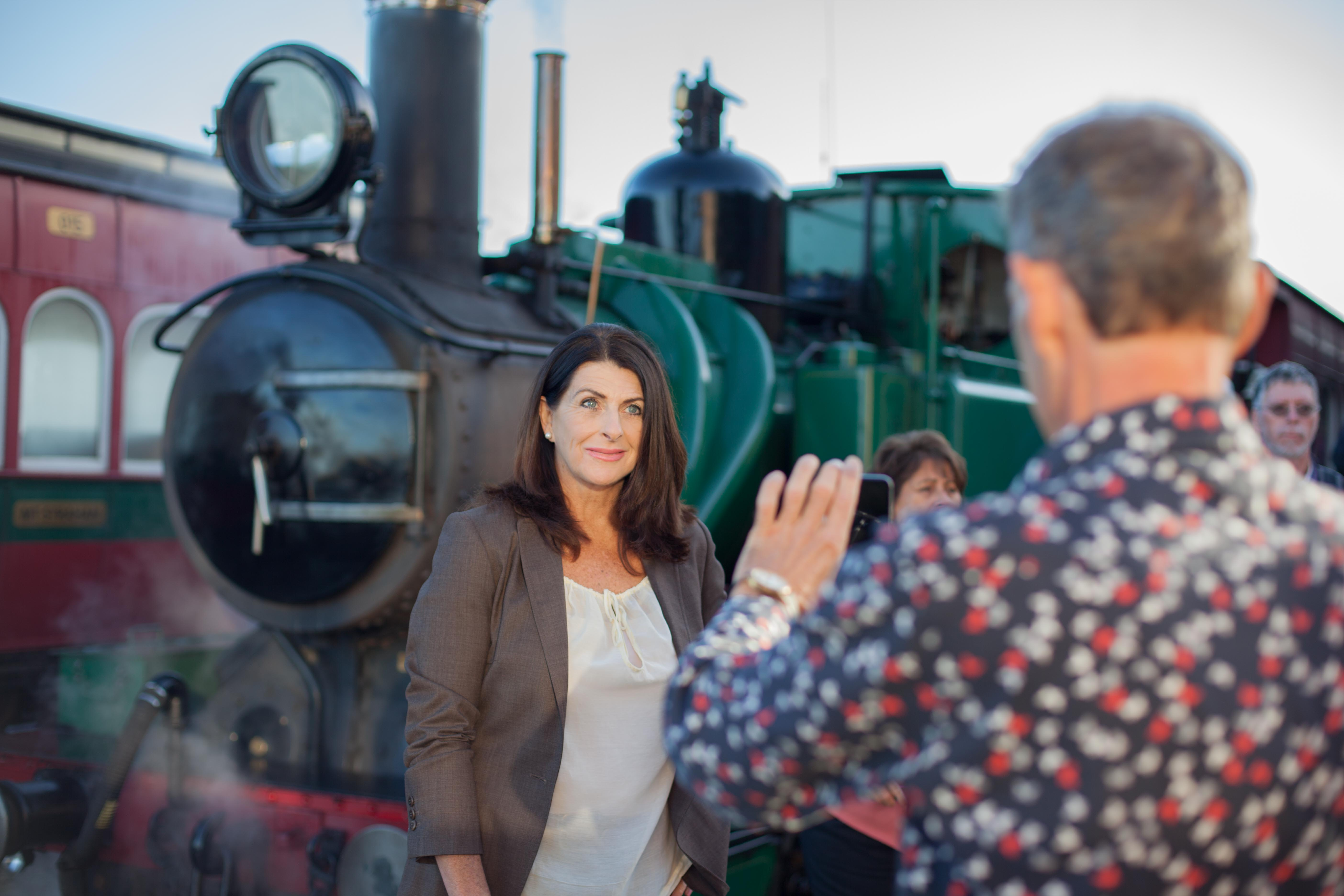 Visitors take photographs by the West Coast Wilderness Railway locomotive