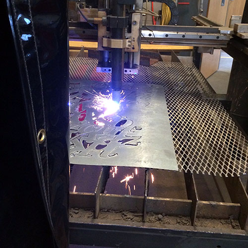 Image of a plasma cutter cutting metal into a typographic skirt.
