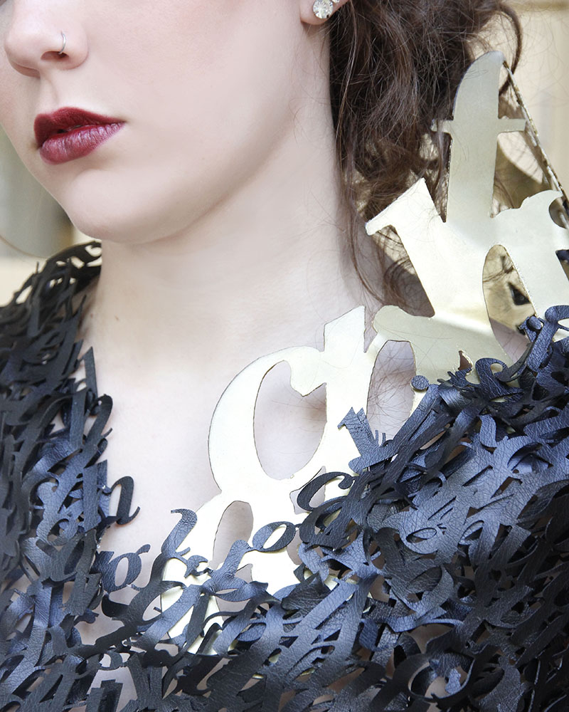 close up of leather typographic top and metal typography colllar.