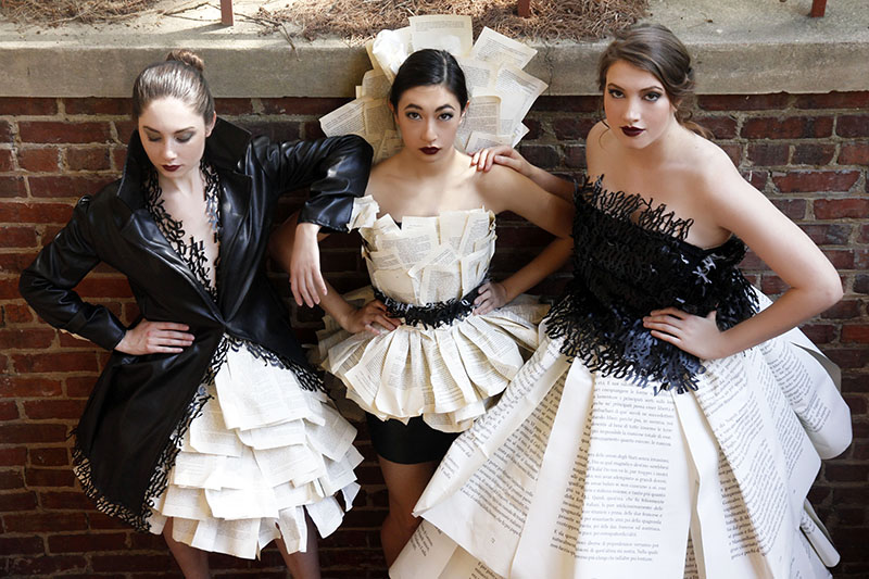 Three models in leather typography and book page dresses.