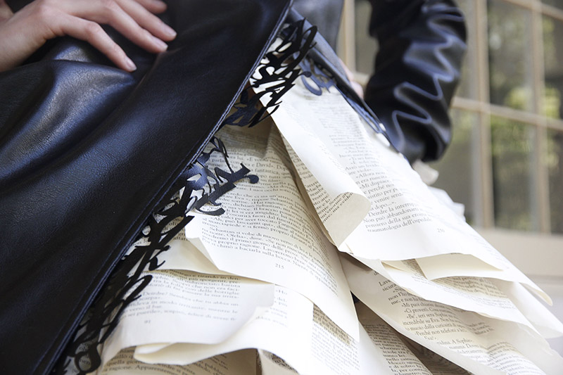 Close up of dress with book page skirt, leather jacket, and leather typography lining.
