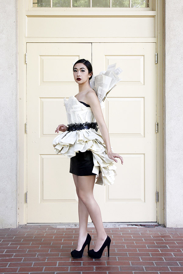 Model in book paper dress and leather mini skirt.