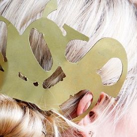 Model with blonde hair and metal typography pin.
