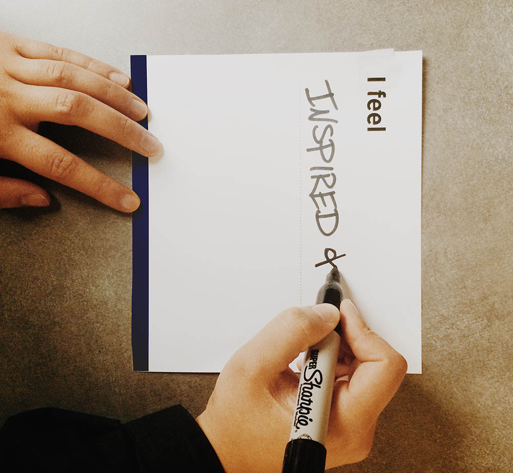 """person writing on a card that says """"I feel... inspired and"""""""