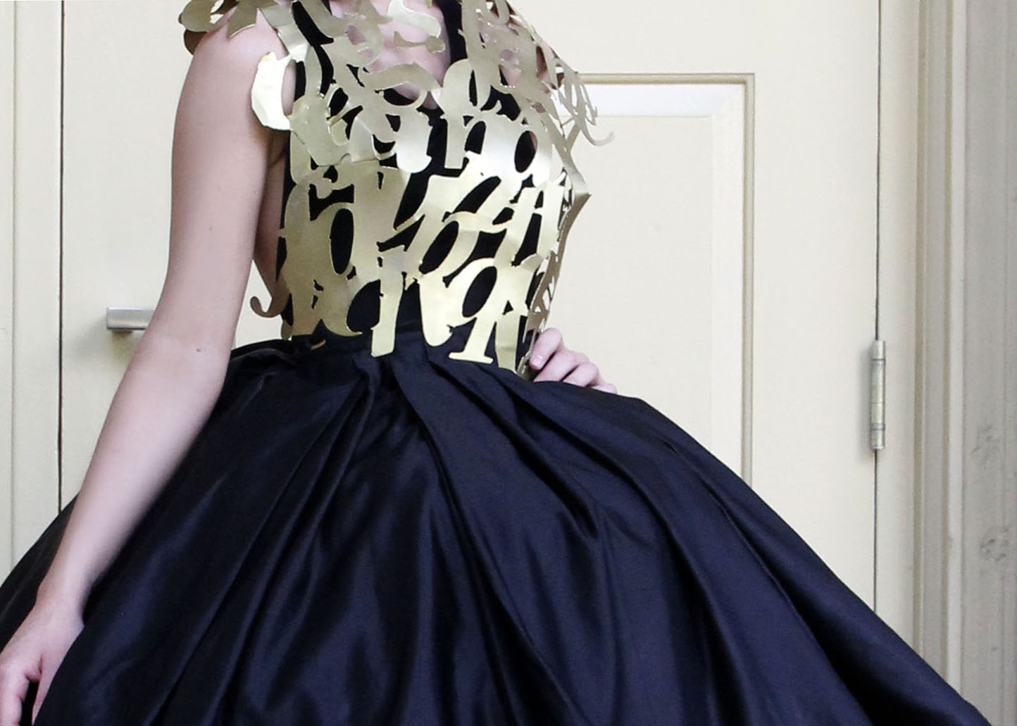 Metal typographic top, like armor, and a wide silk black hoop skirt.