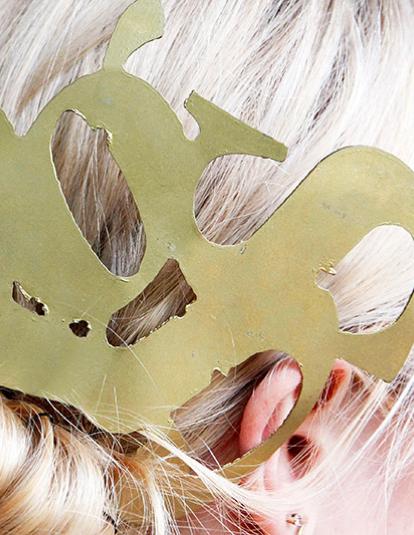 Metal typography hair ornament in model's blonde hair.