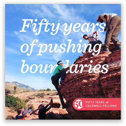 """A man climbing a rock formation with men above and below to help him climb. """"Fifty years of pushing boundaries"""" in text overlaid."""