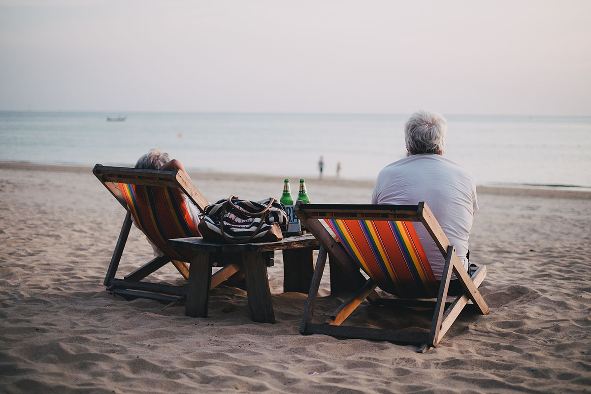 Retired couple on beach in lounge chairs