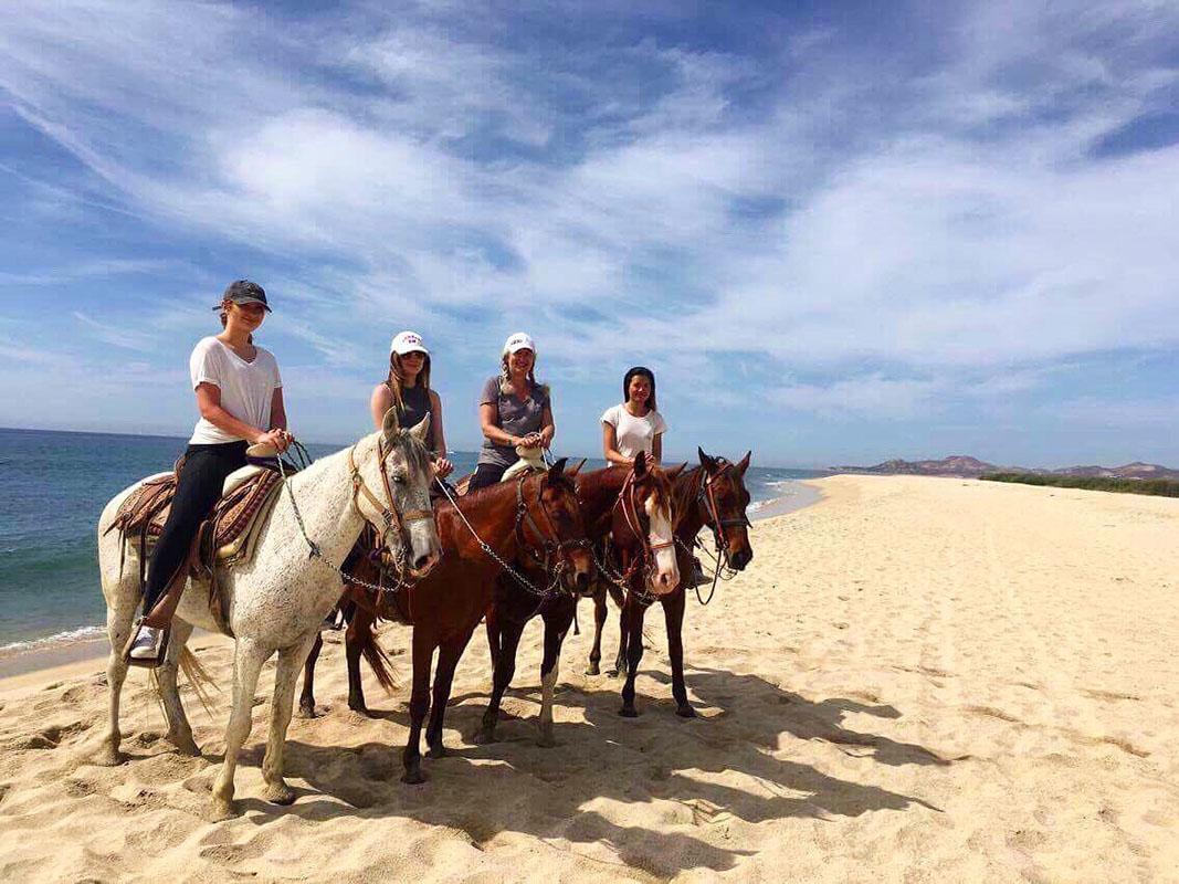 Friends horse riding beach