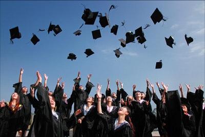 Photo of Graduates throwing caps in air
