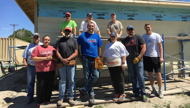 Employees standing in front of a habitat for humanity house