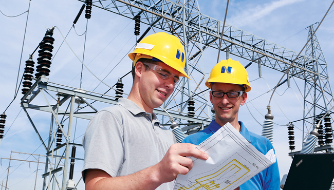 Engineers looking at plans with a substation in background