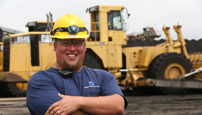 Individual with arms crossed standing in front of heavy equipment