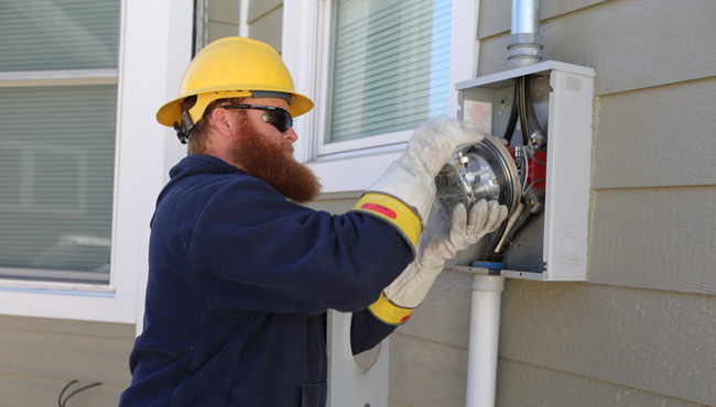 Technician replacing an electric meter on a house