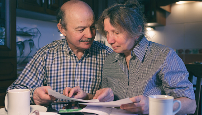 Couple looking concerned when reviewing bills