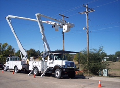 Bucket trucks with boom extended assisting in power restoration