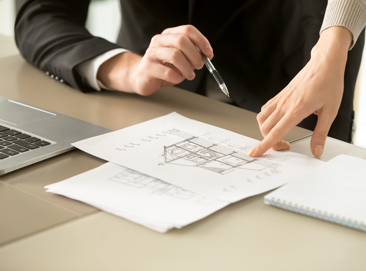 House plans with a persons finger pointing to a certain area