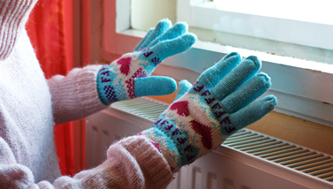 Hands with gloves on warming over heater