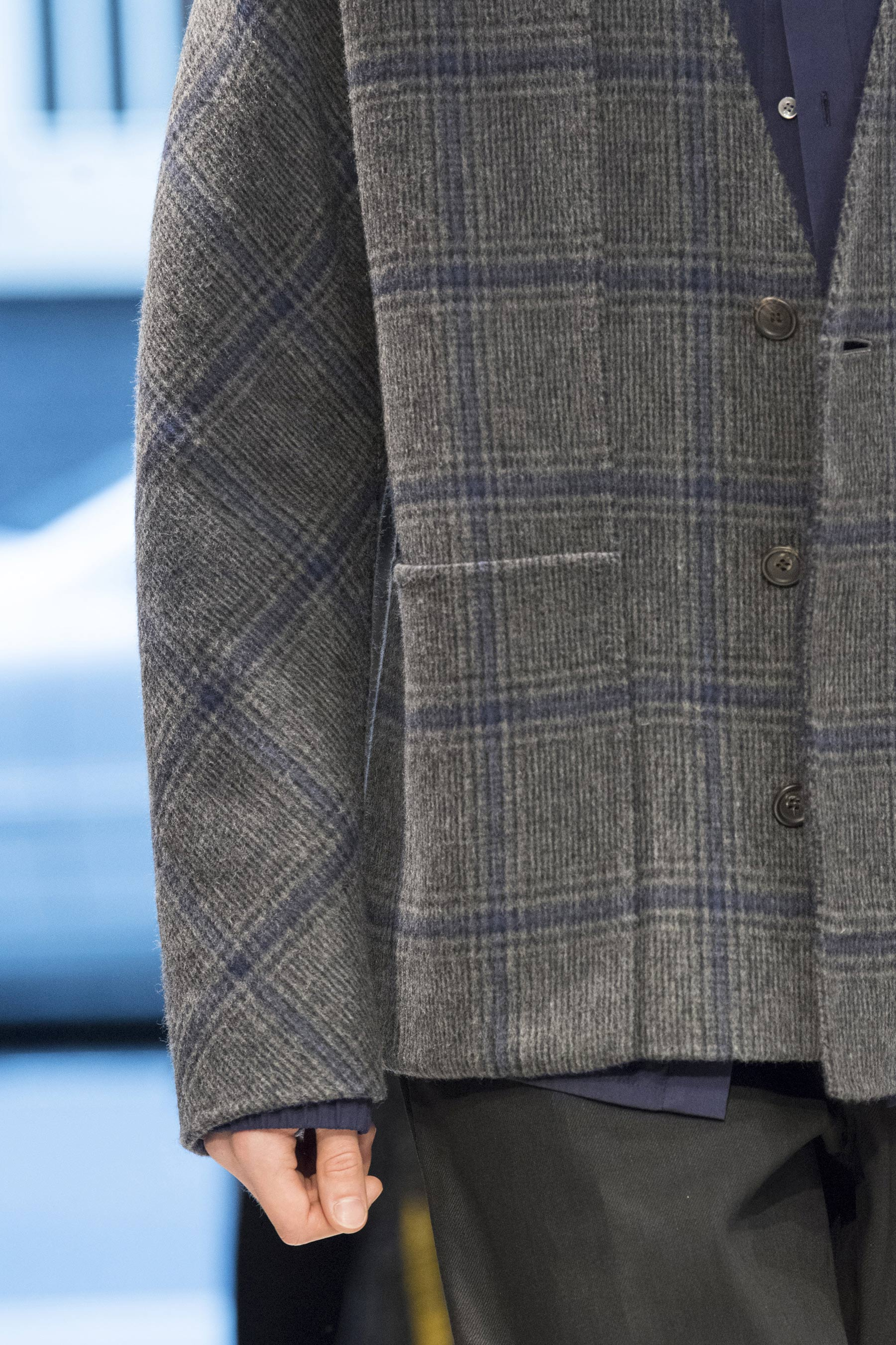 Detail of a checked tweed jacket from Chalayan Men's Fall/Winter 2019 collection shown at London Fashion Week: Men's.
