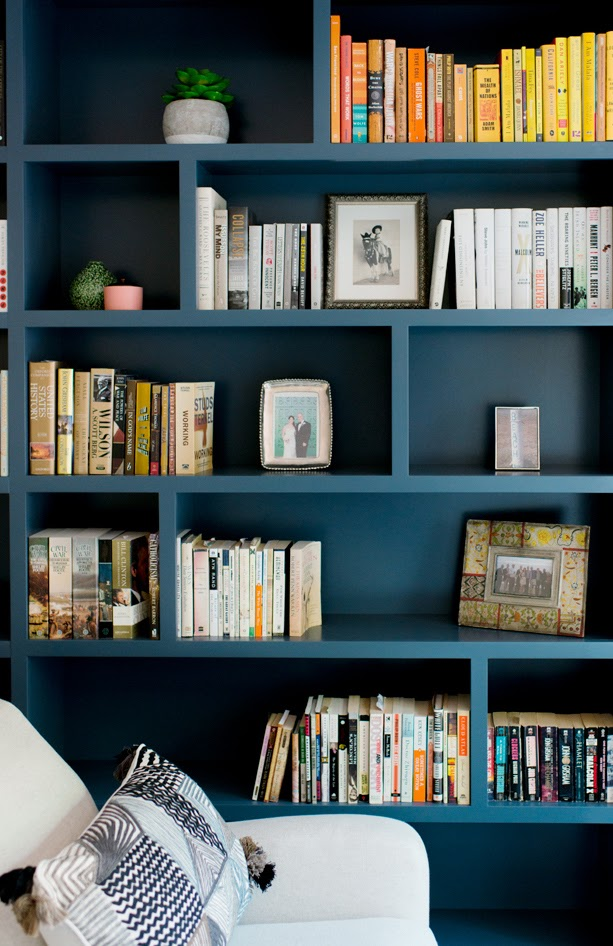 built in book case colorful books frames guest space airbnb comfort necessities joy street design