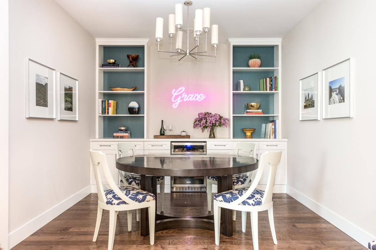 walnut creek interior design dining area wine fridge built in shelving upholstered chairs wallpaper neon sign