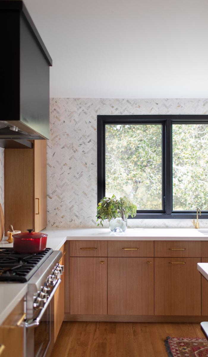 calcutta gold marble herringbone backsplash black range oak cabinets