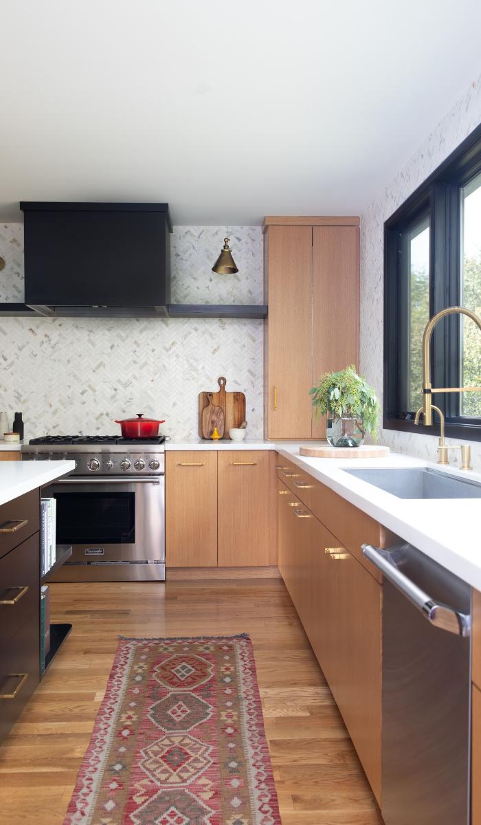 1940s kitchen remodel black range calcutta gold herringbone tile backsplash brass hardware sconces