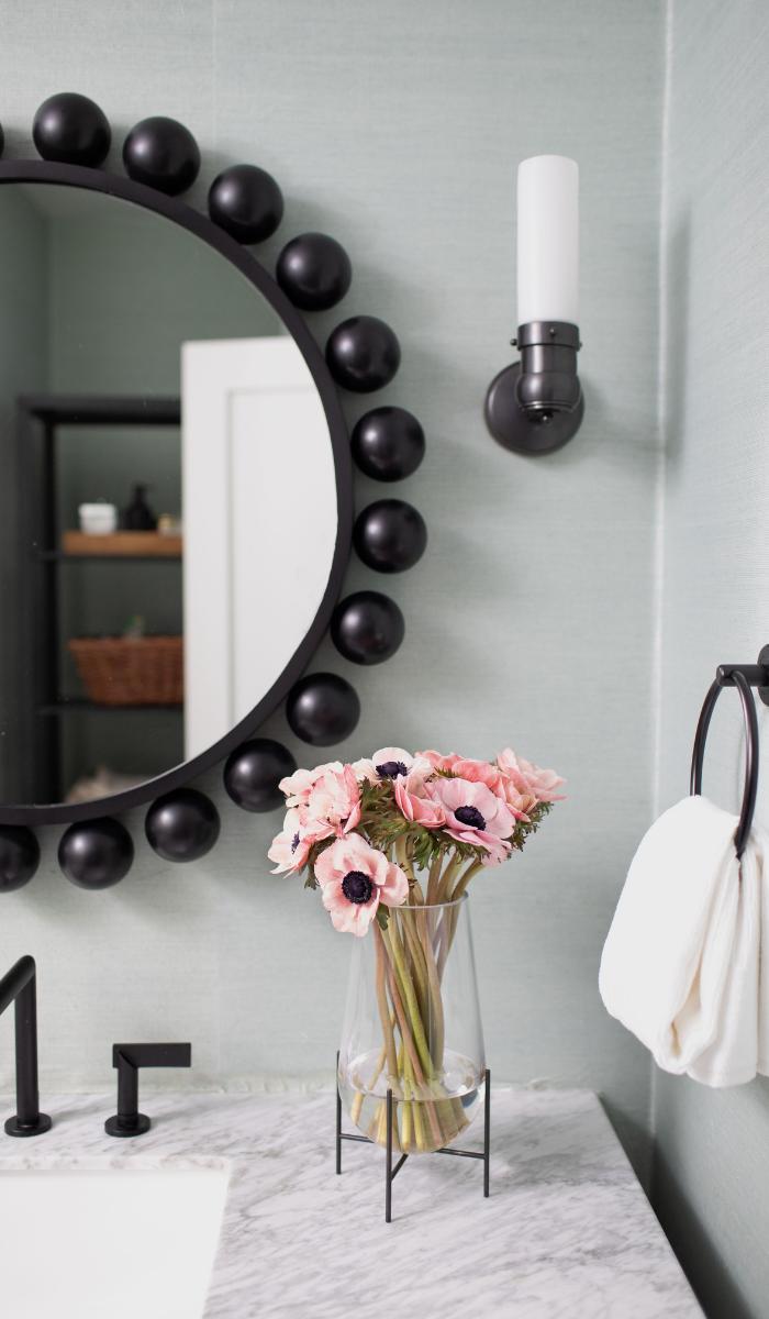 blue grasscloth sconce carrara marble vanity top black mirror bathoom design