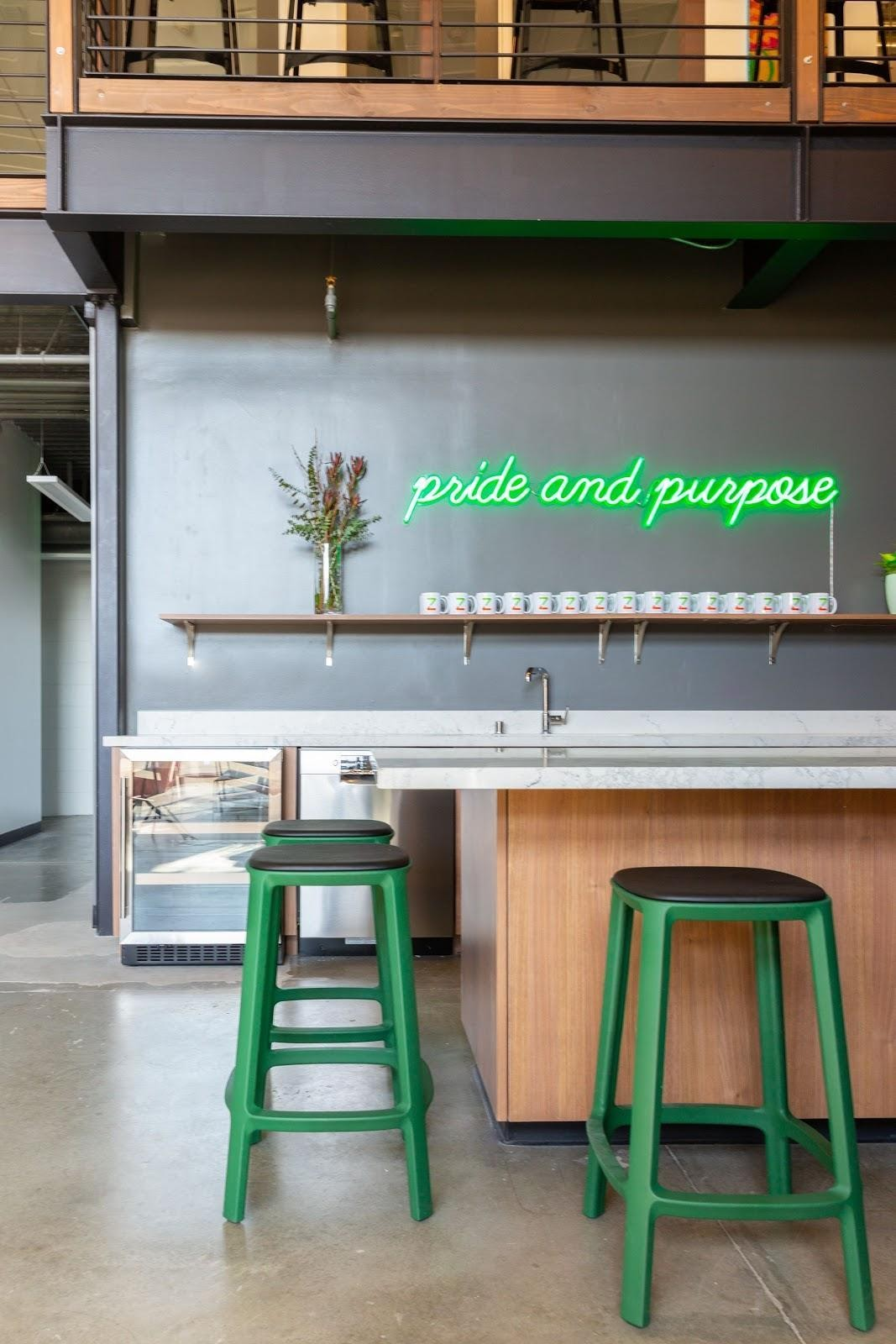 kitchenette pride and purpose neon sign steel wood coworking space green chairs