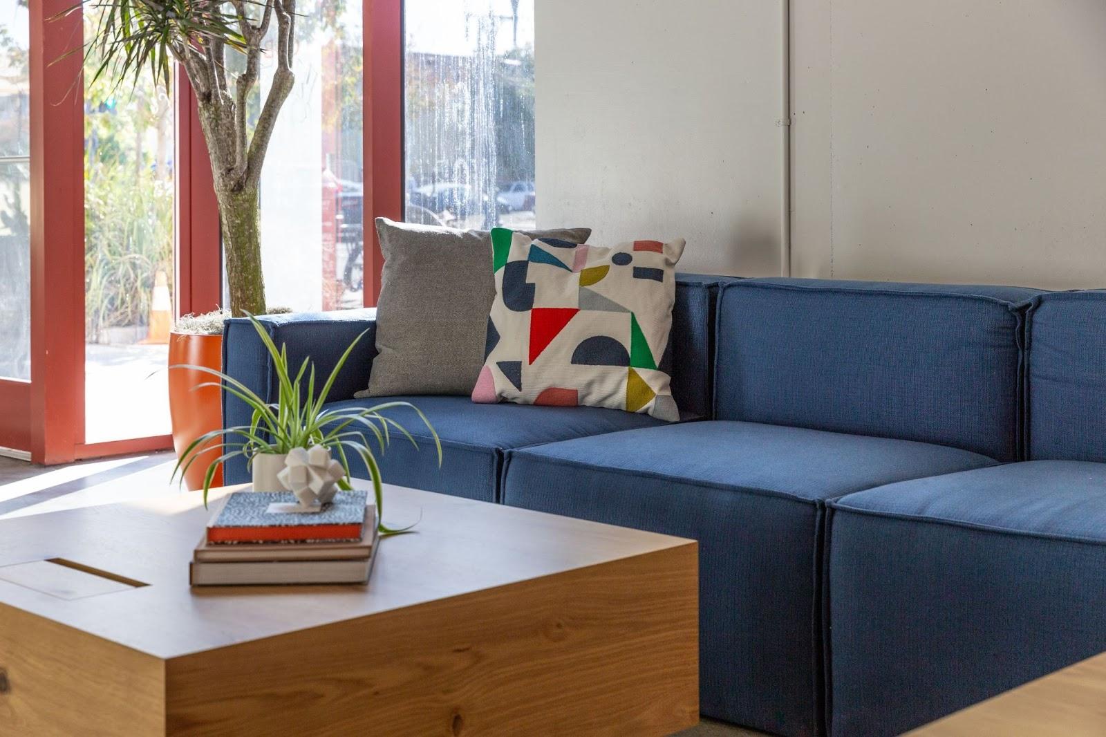 custom sofa olorful pillows orange window frames coworking space