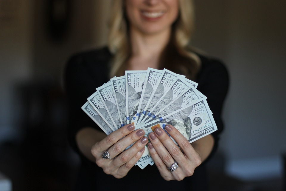 A woman holding a handful of $100 bills