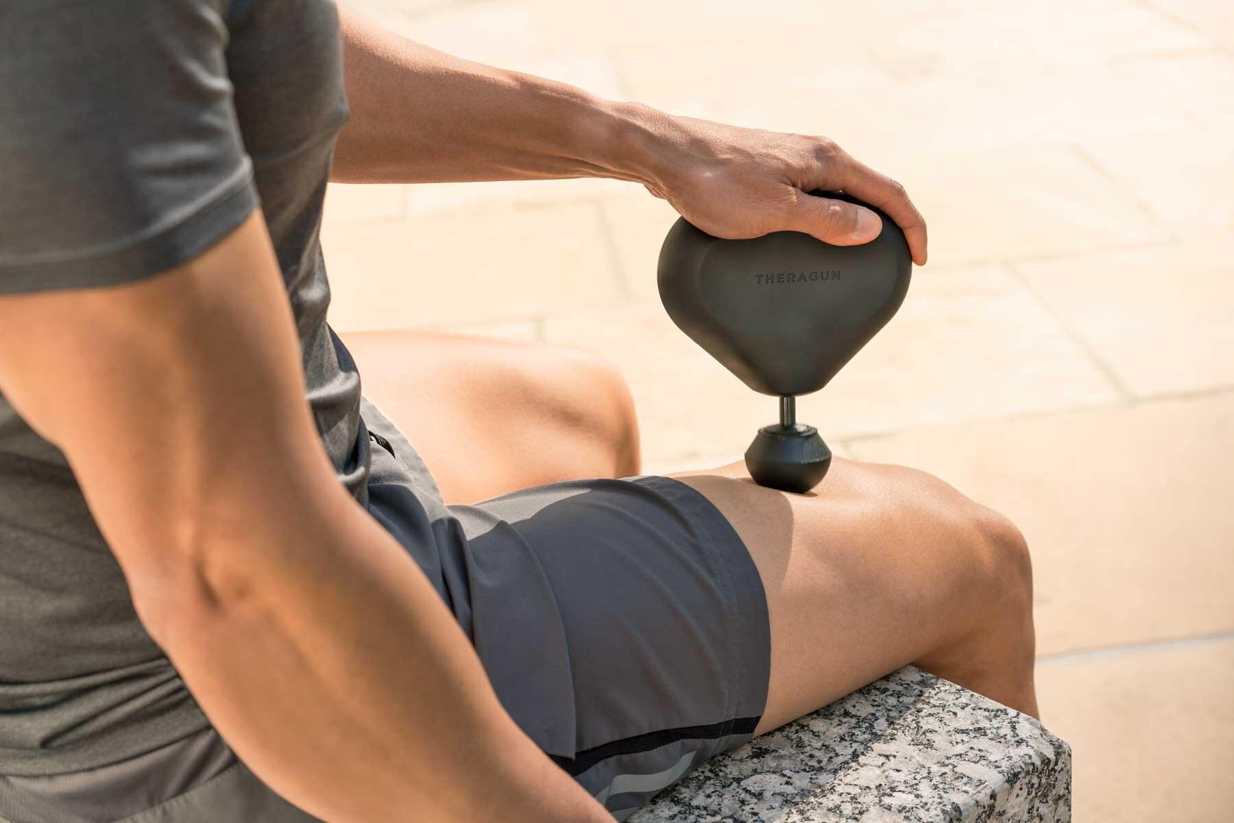 Man using a Theragun Mini massage device