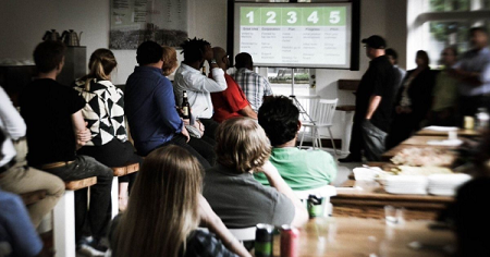 The image shows people who are staying in front of projector screen.