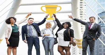 The image shows group of people holding together an award.