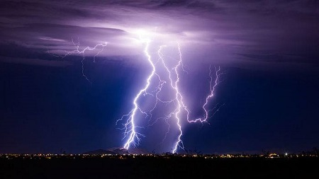 The image is showing a lightning in a dark sky.