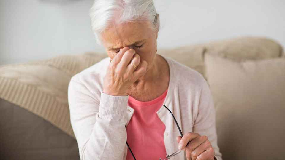 close up of senior woman with glasses sitting on sofa and having headache at home