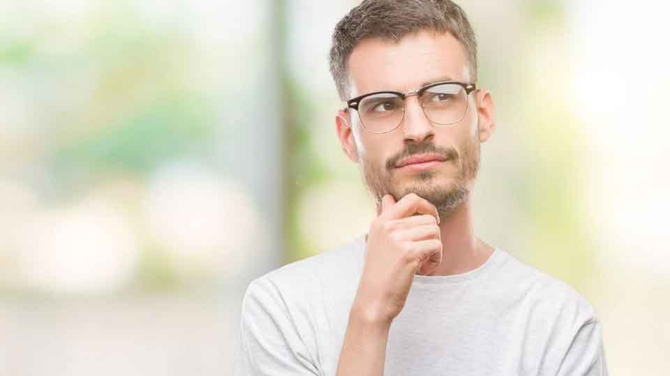 Young adult man wearing glasses with hand on chin thinking about question, pensive expression.