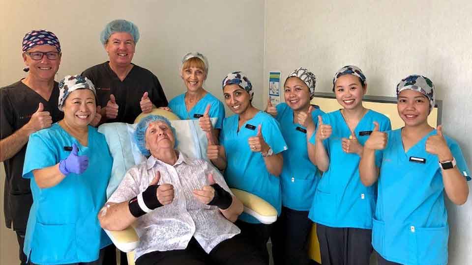Ophthalmologists and team of nurses standing around elderly cataract surgery patient