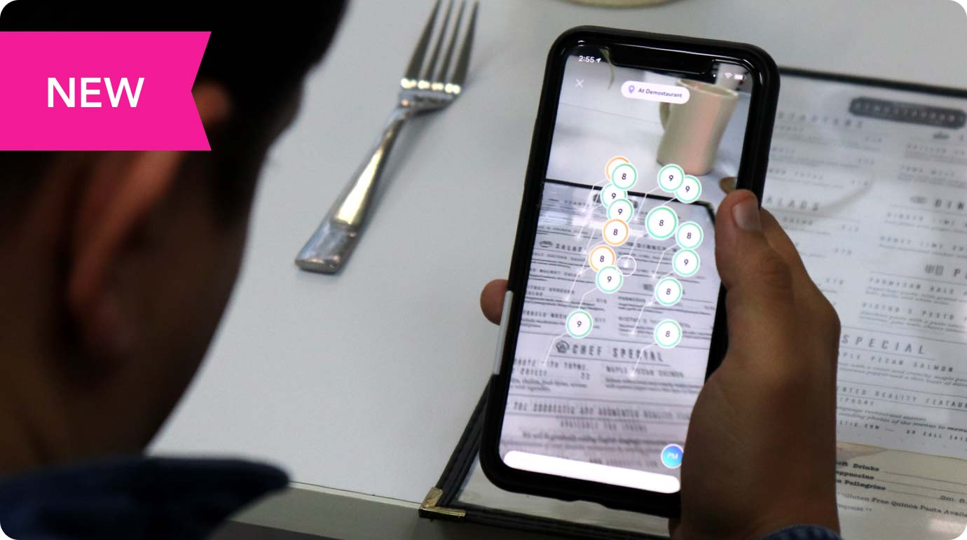 A person holds a phone with Suggestic Lens above a restaurant menu to see the compatibility with their diet.
